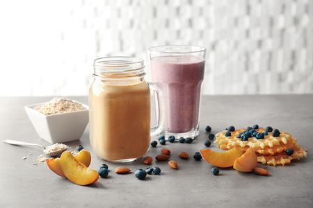 Mason jar and glass with tasty smoothies, wafer and some ingredients on kitchen table