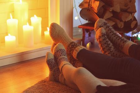 Photo pour Legs in socks near fireplace, close up view - image libre de droit