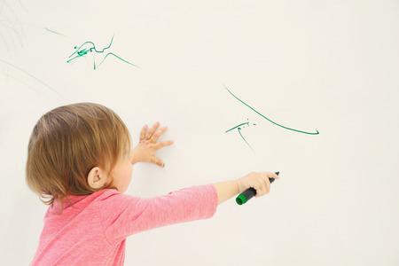 Foto de Cute little girl drawing on light wall - Imagen libre de derechos