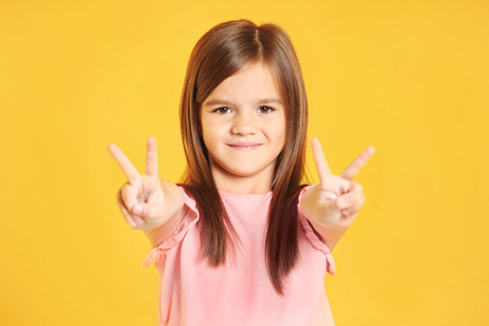 Attractive little girl on yellow background