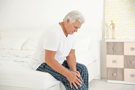 Senior gentleman suffering from pain in bedroom