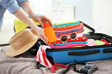 Foto de Female hands packing traveler case on bed, closeup - Imagen libre de derechos
