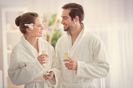 Photo pour Young happy couple drinking champagne in spa salon - image libre de droit