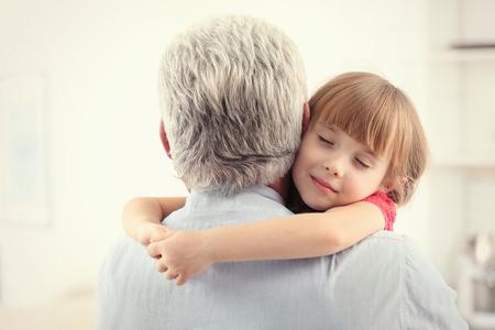 Foto de Girl embracing grand father at home - Imagen libre de derechos