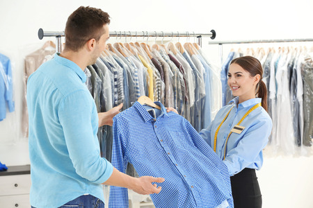 Photo pour Woman working with customer in dry-cleaning salon - image libre de droit