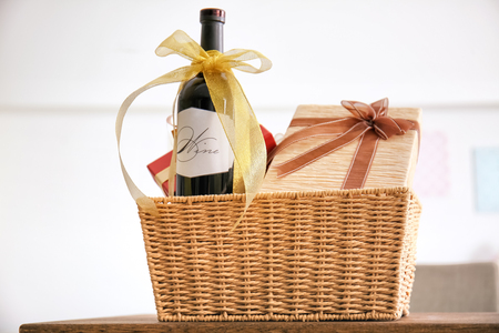 Foto de Wine bottle with gift boxes in wicker basket on light background - Imagen libre de derechos