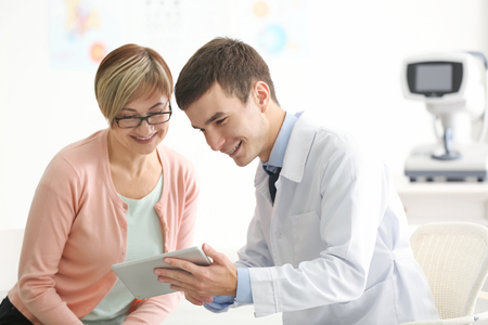 Young ophthalmologist with tablet computer and mature patient in clinic