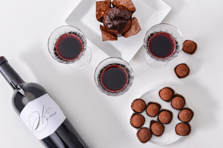 Photo pour Delicious chocolate cake, truffles and red wine on white background - image libre de droit