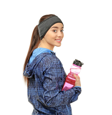 Foto de Young woman in sportswear with bottle on white background - Imagen libre de derechos