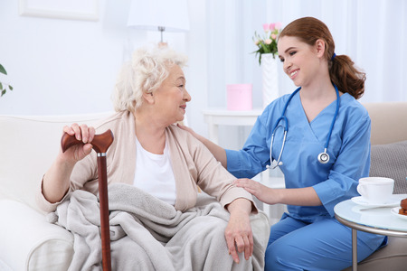 Photo pour Nurse talking with elderly woman in light room - image libre de droit
