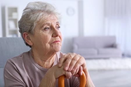 Foto de Elderly woman with walking stick at home - Imagen libre de derechos