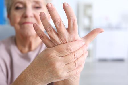 Foto de Elderly woman suffering from pain in hand, closeup - Imagen libre de derechos