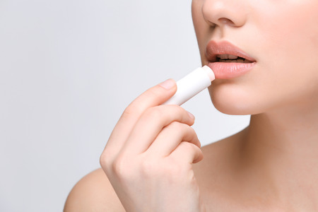 Foto de Woman applying hygienic lip balm on light background - Imagen libre de derechos