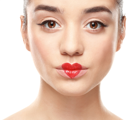 Photo pour Portrait of beautiful young woman with heart painted on lips, against white background - image libre de droit