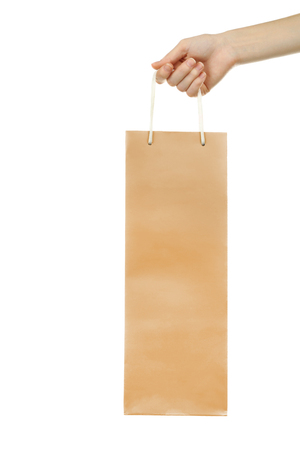 Foto de Female hand holding gift paper bag on white background - Imagen libre de derechos