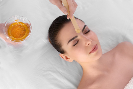 Photo pour Beautician depilating young woman's face with wax in spa center - image libre de droit