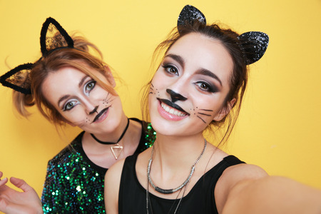 Foto de Beautiful young women with cat makeup and ears on color background - Imagen libre de derechos