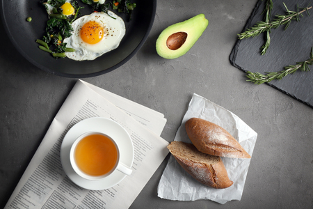 Pan with tasty fried eggs and cup of tea on gray background