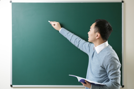 Photo pour Handsome young Asian teacher writing on blackboard - image libre de droit