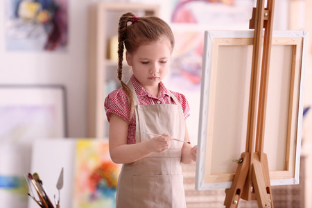 Foto de Cute little artist painting picture in studio - Imagen libre de derechos