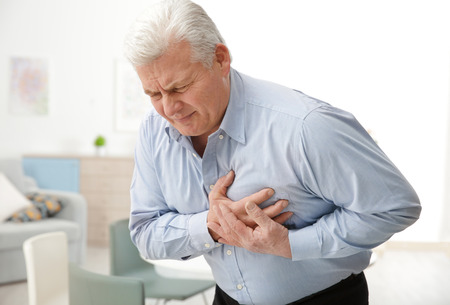 Photo pour Man with chest pain suffering from heart attack in office - image libre de droit
