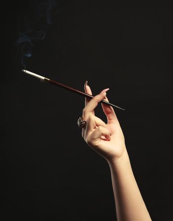 Female hand with cigarette holder on dark background