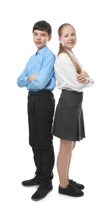Foto de Cute boy and girl in school uniform standing on white background - Imagen libre de derechos