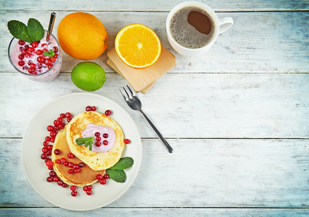 Tasty pancakes with yogurt and fruits on table