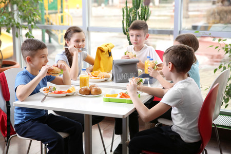 Foto de Children sitting at cafeteria table while eating lunch - Imagen libre de derechos