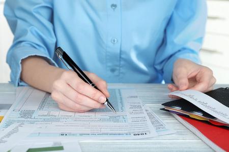 Photo pour Woman filling form of Individual Income Tax Return, closeup - image libre de droit