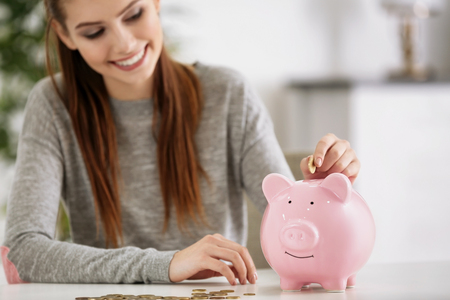 Photo pour Beautiful young woman putting coins into piggy bank at home - image libre de droit