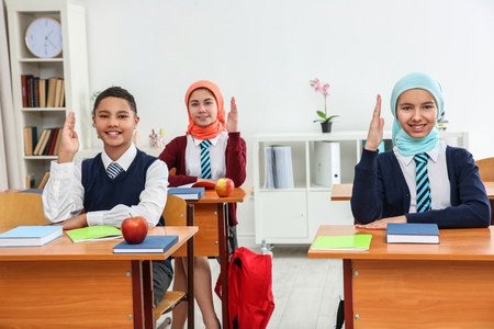 Photo pour Schoolchildren sitting at desks in classroom - image libre de droit