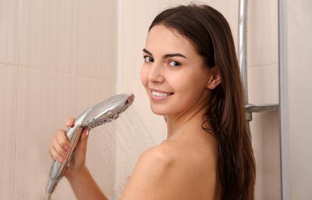 Beautiful young woman taking shower