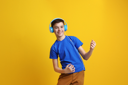 Foto de Teenager with headphones listening to music on color background - Imagen libre de derechos