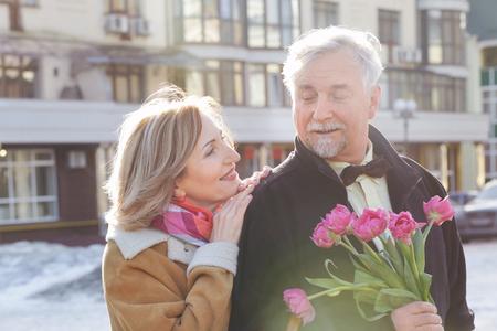 Foto de Happy senior couple with bouquet of flowers  on a walk - Imagen libre de derechos
