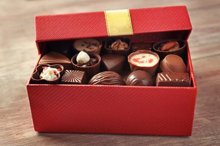 Photo pour Gift box with delicious candies on wooden background - image libre de droit