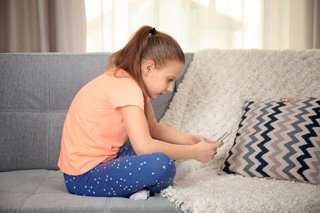 Foto de Incorrect posture concept. Cute schoolgirl with phone sitting on sofa - Imagen libre de derechos