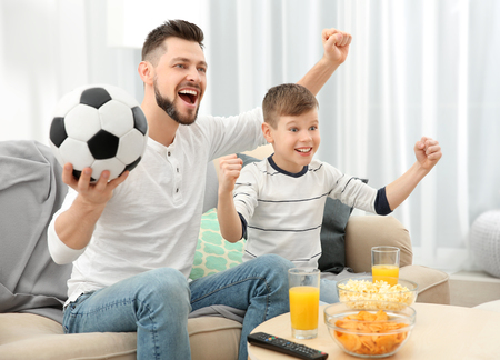 Photo pour Father and son watching football on TV at home - image libre de droit