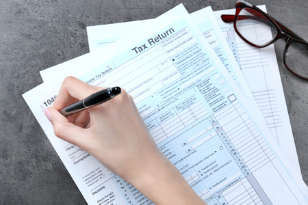 Photo pour Woman filling in individual income tax form, closeup - image libre de droit