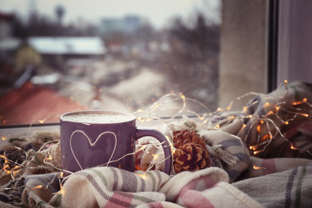 Photo pour Cup of hot tasty coffee with garland and warm plaid on windowsill - image libre de droit