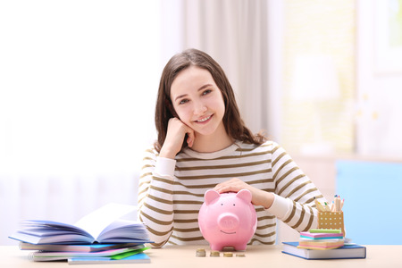 Foto de Smiling girl sitting at table with piggy bank and stationery. Saving for education concept - Imagen libre de derechos