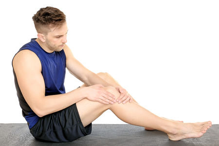 Sporty young man suffering from pain in leg on white background