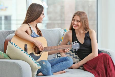 Photo pour Lovely lesbian couple with guitar in light room - image libre de droit