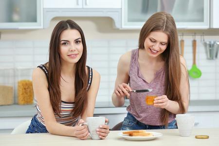 Photo pour Lovely lesbian couple having breakfast together in light kitchen - image libre de droit