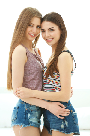 Photo pour Lovely lesbian couple hugging in light room - image libre de droit