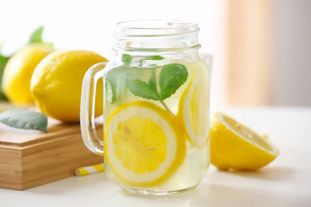 Foto de Glass jar with lemonade on light table - Imagen libre de derechos