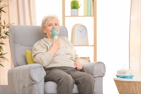 Photo pour Elderly woman using asthma machine at home - image libre de droit