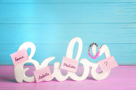 Word BABY and paper stickers with different names on color wooden background. Concept of choosing baby name
