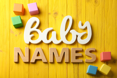 Words BABY NAMES on color wooden background. Concept of choosing baby name
