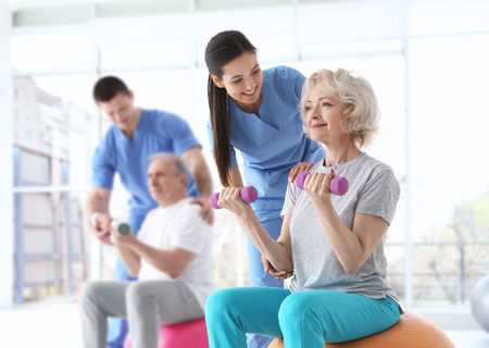 Photo pour Physiotherapists working with elderly patients in modern clinic - image libre de droit